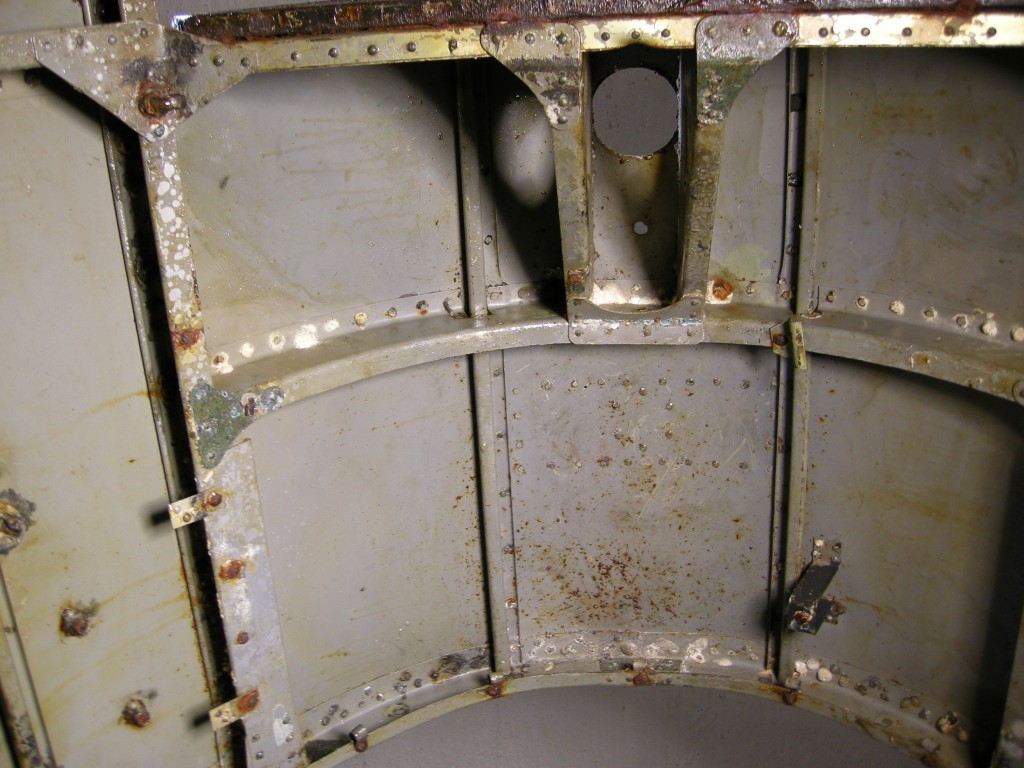 The top between ribs 4 and 5. Cylinder for height adjustment of the pilot's seat height was mounted in the hole.