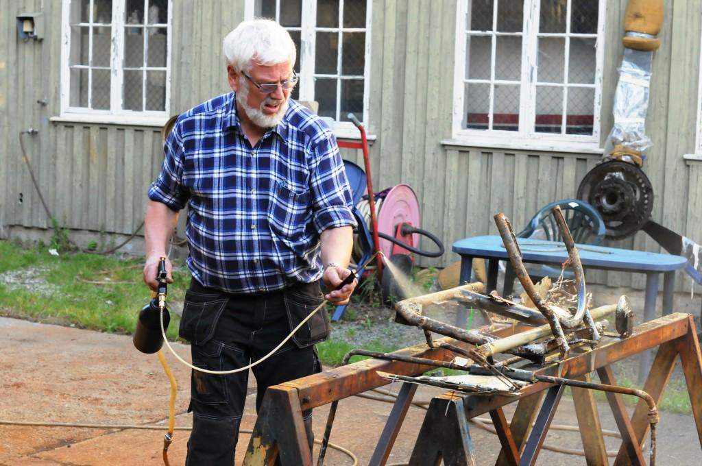 Roar Henriksen i gang med å sprøyte Lanolin på ferdig rengjorte smådeler.